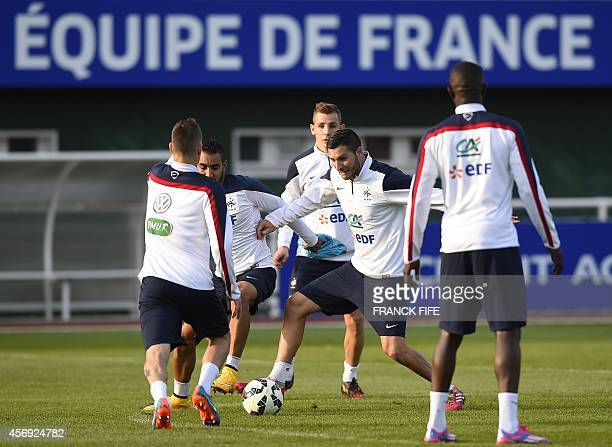 France's midfielder Dimitri Payet vies with France's forward Andre Pierre Gignac during a training session in ClairefontaineenYvelines on October 9...