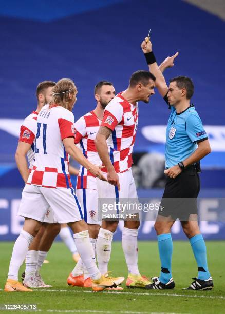 France's midfielder Eduardo Camavinga complains as he is given a yellow card by the referee Ovidiu Hategan during the UEFA Nations League Group C...