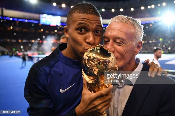TOPSHOT France's midfielder Kylian Mbappe and France's coach Didier Deschamps kiss the 2018 World Cup trophy as they celebrate during a ceremony for...