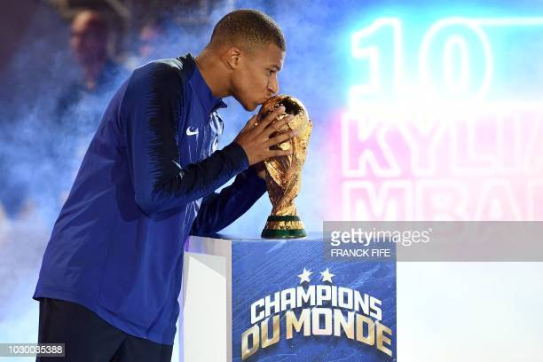 France's midfielder Kylian Mbappe kisses the 2018 World Cup trophy during a ceremony to celebrate the victory of the 2018 World Cup before the lap of...