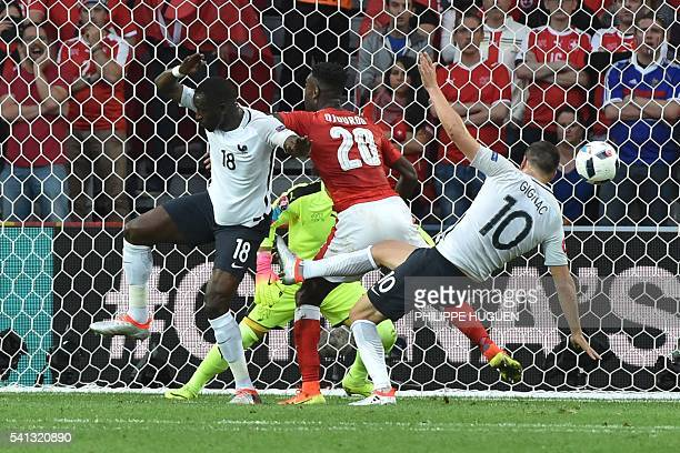 France's midfielder Moussa Sissoko and France's forward AndrePierre Gignac vie for the ball with Switzerland's defender Johan Djourou during the Euro...