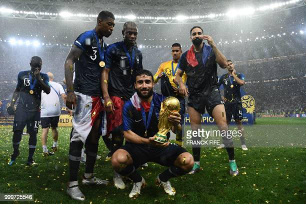 France's midfielder Nabil Fekir holds the World Cup trophy as he celebrates with teammates winning the Russia 2018 World Cup final football match...