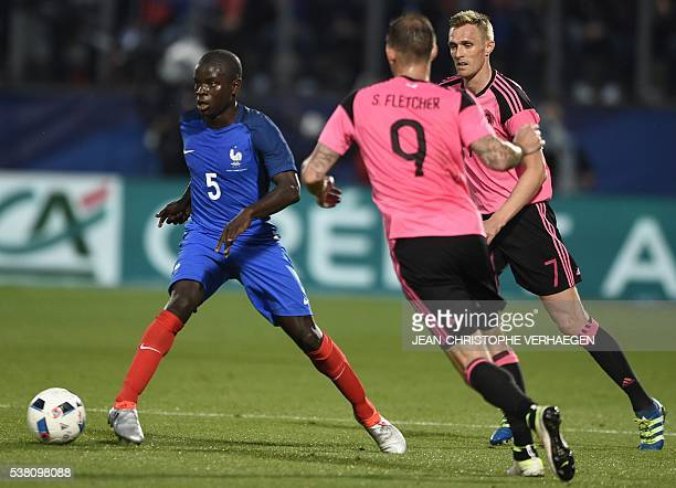 France's midfielder N'Golo Kante fights for the ball with Scotland's forward Steven Fletcher and Scotland's midfielder Darren Fletcher during the...