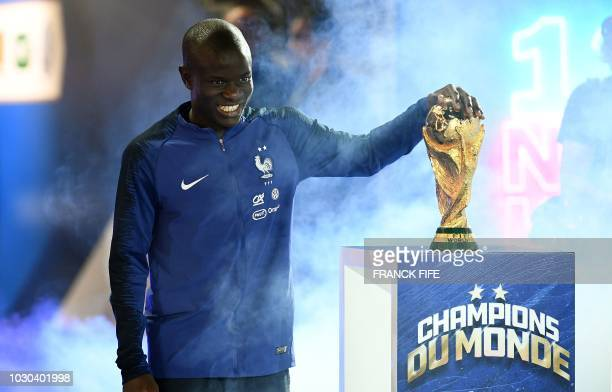 France's midfielder N'Golo Kante looks the 2018 World Cup trophy during a ceremony to celebrate the victory of the 2018 World Cup before the lap of...