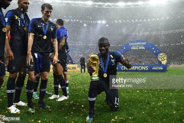 France's midfielder N'Golo Kante poses with the World Cup trophy during the trophy ceremony at the end of the Russia 2018 World Cup final football...