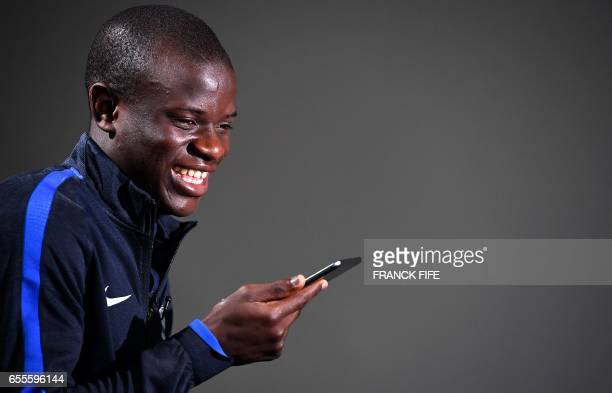 France's midfielder N'Golo Kante reacts during a press conference in Clairefontaine near Paris on March 20 as part of the team's preparation for the...