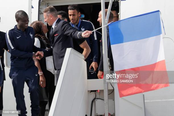 France's midfielder N'Golo Kante shakes hands with a member of plane staff as he disembarks with teammates upon their arrival at the RoissyCharles de...