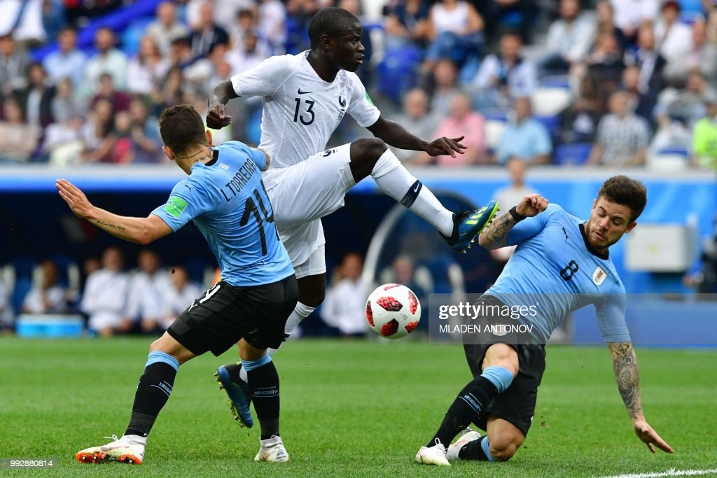 France's midfielder N'Golo Kante (C) vies with Uruguay's midfielder Lucas Torreira (L) and Uruguay's midfielder Nahitan Nandez during the Russia 2018 World Cup quarter-final football match between Uruguay and France at the Nizhny Novgorod Stadium in Nizhny Novgorod on July 6, 2018.