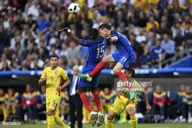 France's midfielder Paul Pogba and France's defender Laurent Koscielny vie for the ball against Romania's forward Florin Andone as Romania's...