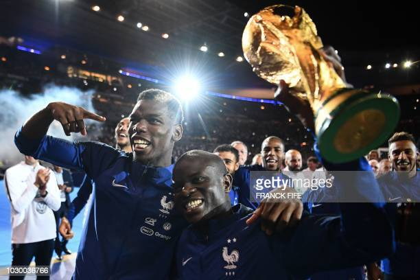 France's midfielder Paul Pogba and France's defender N'golo Kante hold the 2018 World Cup trophy as they celebrate during a ceremony for the victory...