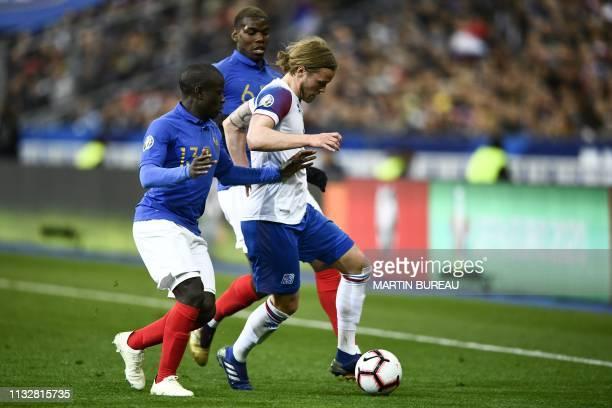 France's midfielder Paul Pogba and France's midfielder N'Golo Kante vie for the ball with Iceland's midfielder Birkir Bjarnason during the UEFA Euro...