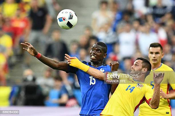 France's midfielder Paul Pogba and Romania's forward Florin Andone vie for the ball during the Euro 2016 group A football match between France and...