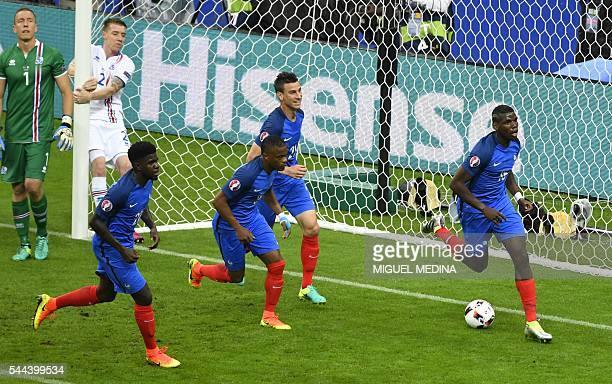 France's midfielder Paul Pogba celebrates after scoring his team's second goal during the Euro 2016 quarterfinal football match between France and...