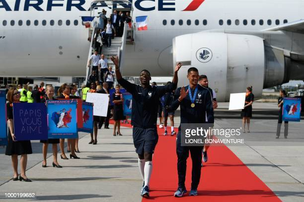 France's midfielder Paul Pogba celebrates and greets the fans as he disembarks from the plane with France's goalkeeper Alphonse Areola upon their...