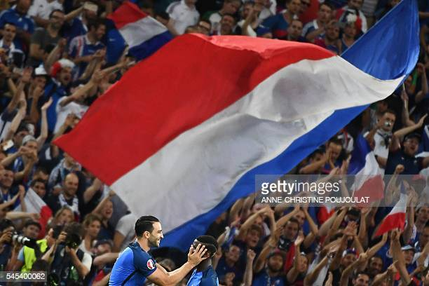 France's midfielder Paul Pogba celebrates with France's defender Adil Rami after winning the Euro 2016 semifinal football match between Germany and...