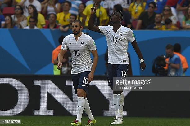 France's midfielder Paul Pogba celebrates with France's forward Karim Benzema after scoring the first goal during a Round of 16 football match...