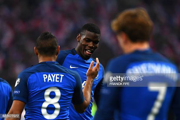 France's midfielder Paul Pogba celebrates with France's midfielder Dimitri Payet after scoring a goal during the 2018 World Cup group A qualifying...