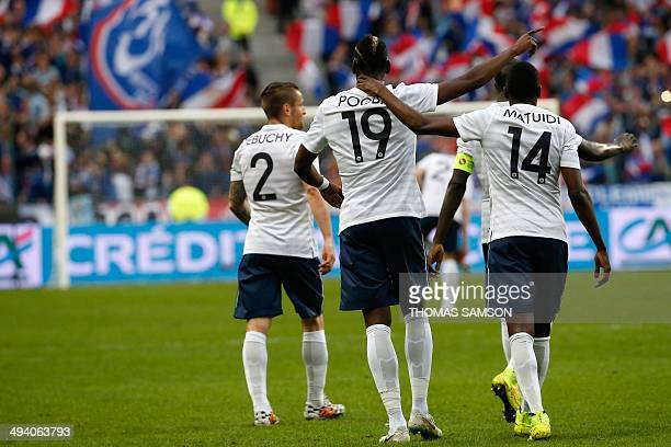 France's midfielder Paul Pogba celebrates with teammates defender Mathieu Debuchy and midfielder Blaise Matuidi after he scored a goal during the...
