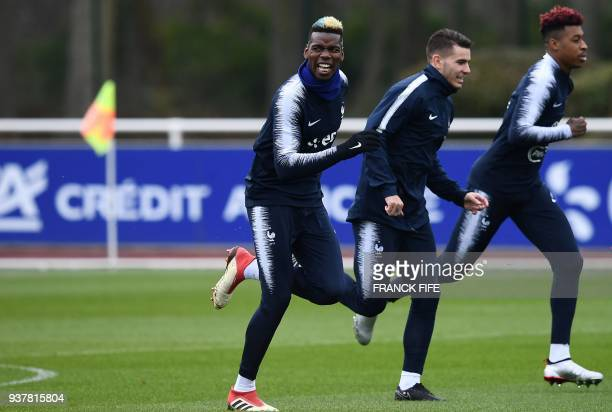 France's midfielder Paul Pogba France's defender Lucas Hernandez and France's defender Presnel Kimpembe warm up during a training session in...