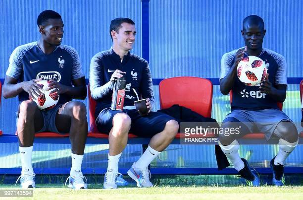 France's midfielder Paul Pogba France's forward Antoine Griezmann France's midfielder N'Golo Kante sit on the bench during a training session at the...