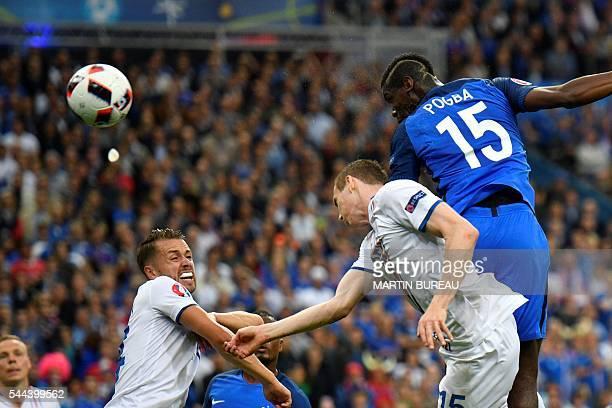 France's midfielder Paul Pogba heads the ball to score a goal past Iceland's forward Jon Dadi Bodvarsson during the Euro 2016 quarterfinal football...