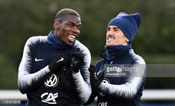TOPSHOT France's midfielder Paul Pogba jokes with France's forward Antoine Griezmann during a training session in ClairefontaineenYvelines on March...