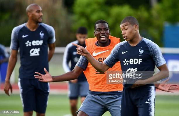 France's midfielder Paul Pogba jokes with France's forward Kylian Mbappe at the end of a training session in Clairefontaine en Yvelines on May 30 as...