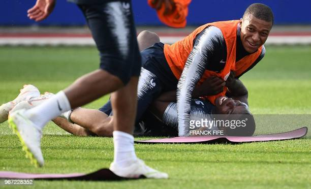 France's midfielder Paul Pogba jokes with France's forward Kylian Mbappe at the end of a training session in Clairefontaine-en-Yvelines on June 4 as...