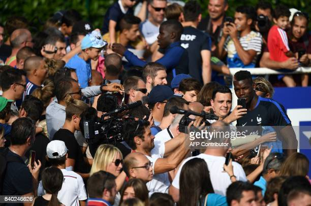 France's midfielder Paul Pogba poses with fans during a training session in Clairefontaine en Yvelines on August 28 as part of the team's preparation...