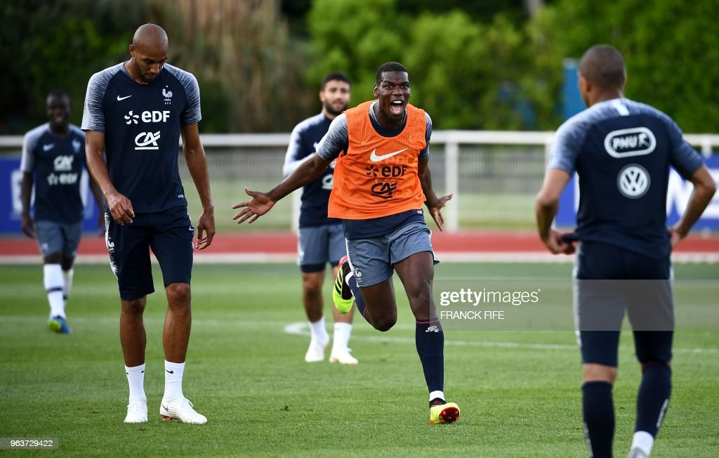 France's midfielder Paul Pogba (C) reacts next to France's forward Kylian Mbappe (R) and France's midfielder Steven N'zonzi at the end of a training session in Clairefontaine en Yvelines on May 30, 2018, as part of the team's preparation for the upcoming FIFA World Cup 2018 in Russia.