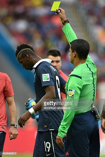 France's midfielder Paul Pogba receives a yellow card from Brazilian referee Sandro Meira Ricci during a Group E football match between France and...