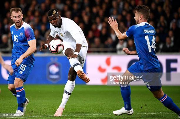 France's midfielder Paul Pogba shoots next to Iceland's midfielder Kari Arnason during the friendly football match between France and Iceland at the...