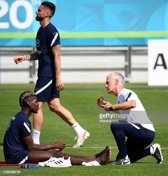 France's midfielder Paul Pogba speaks with France's head coach Didier Deschamps as France's forward Olivier Giroud walks past at the end of a...