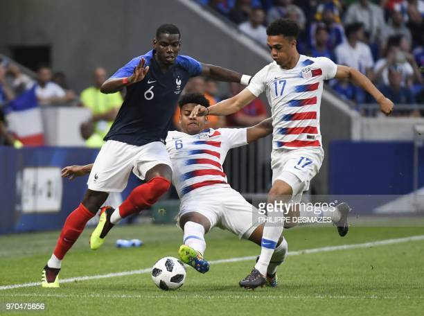 France's midfielder Paul Pogba vies with USA's defender Antonee Robinson and USA's midfielder Weston McKennie during the friendly football match...