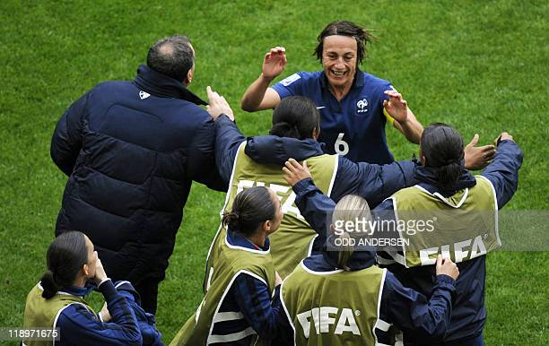 France's midfielder Sandrine Soubeyrand celebrates with France's head coach Bruno Bini and teammates after France's defender Sonia Bompastor scored...