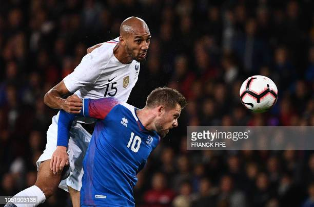 France's midfielder Steven N'zonzi heads the ball behind Iceland's midfielder Gylfi Sigurdsson during the friendly football match between France and...