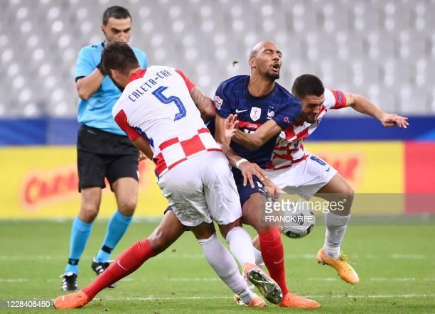 France's midfielder Steven Nzonzi vies for the ball with Croatia's defender Duje Caleta-Car and Croatia's midfielder Mateo Kovacicv during the UEFA...