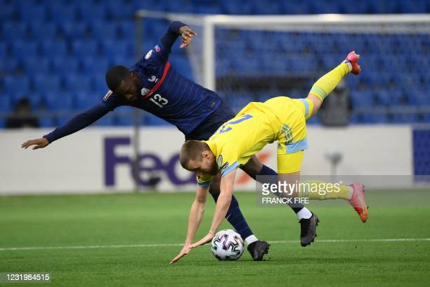 France's midfielder Tanguy Ndombele fights for the ball with with Kazakhstan's midfielder Maxim Fedin during the FIFA World Cup Qatar 2022...