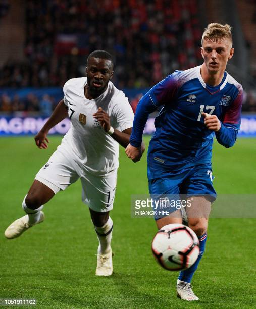 France's midfielder Tanguy Ndombele vies with Iceland's forward Albert Gudmundsson during the friendly football match between France and Iceland at...