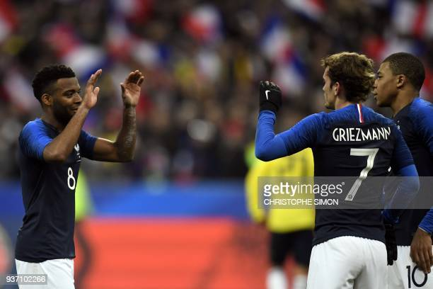 France's midfielder Thomas Lemar celebrates with teammates after scoring a goal during the friendly football match between France and Colombia at the...