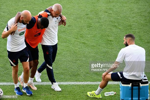 France's midfielder Thomas Lemar leaves the pitch after being injured, helped by staff members past France's forward Karim Benzema during a training...