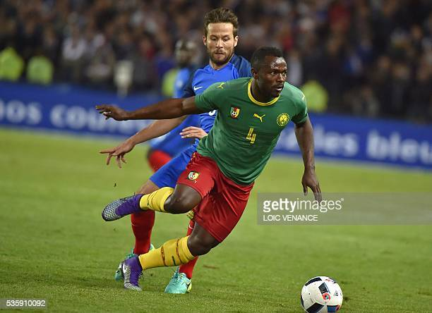 France's midfielder Yohan Cabaye fights for the ball with Cameroon's midfielder Franck Kom during the International friendly football match between...