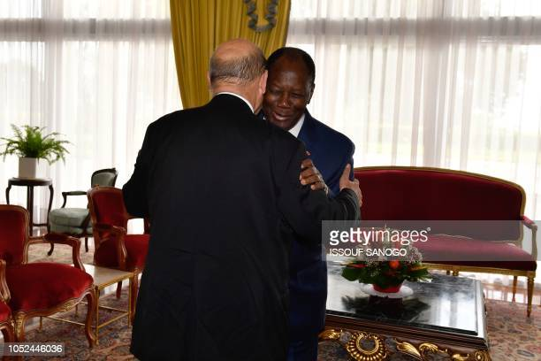France's Minister for Foreign Affairs Jean-Yves Le Drian is welcomed by Ivory Coast's President Alassane Ouattara upon his arrival at the...