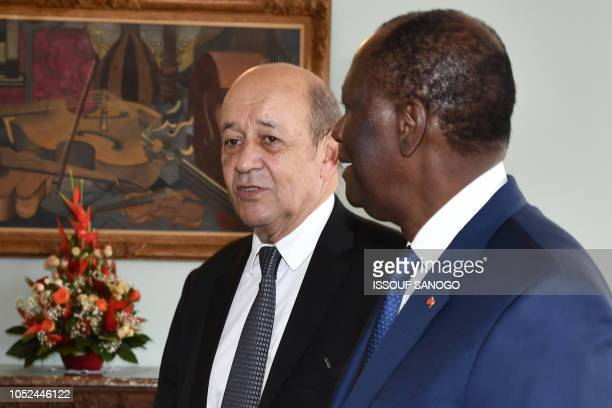 France's Minister for Foreign Affairs Jean-Yves Le Drian stands past Ivory Coast's President Alassane Ouattara upon his arrival at the presidential...