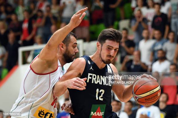 France's Nando De Colo fights for the ball with Bulgaria's Pavel Marinov during the 2019 FIBA European qualifying basketball match between Bulgaria...