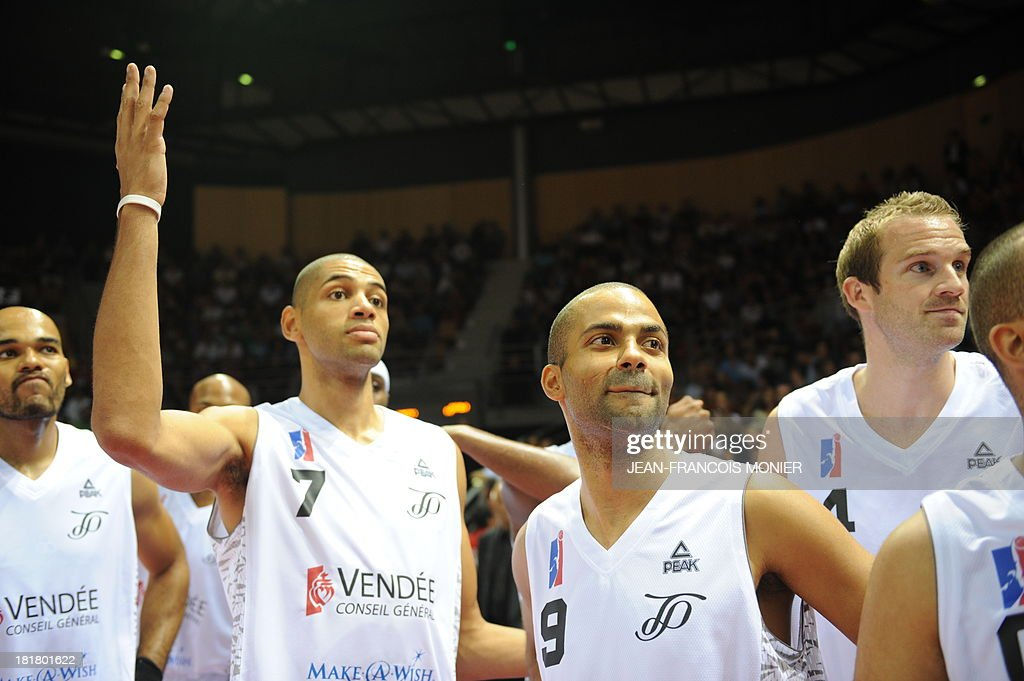 France's national basketball team point guard Tony Parker (2nd R) looks on before the the exibition match Tony Parker Team vs Lyon-Villeurbanne on September 25, 2013 at the Vendespace in Mouilleron-le-Captif, Western France.