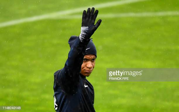 France's national football forward Kylian Mbappe rises his arms during a training session in Clairefontaine en Yvelines on June 5, 2019 as part of...