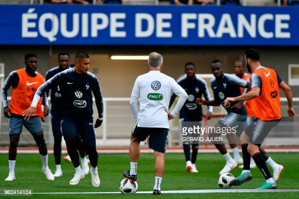 France's national football team coach Didier Deschamps stands as his players train during a training session at the team's training camp in...
