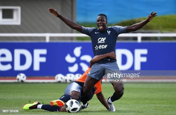 France's national football team defender Benjamin Mendy is tackled by midfielder Paul Pogba during a training session at the team's training cam in...