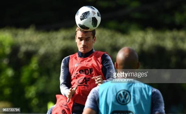 France's national football team forward Antoine Griezmann heads the ball during a training session at their training camp in...